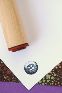 This wonderful button stamp is mounted on a hardwood peg that is 3 1/2-inches long. The stamped image is approximately 5/8 inch wide.    These stamps
