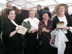 "Several actors pose with ""food"" brought in during a reenactment of the arrival of food ships during the 1913 Lockout."