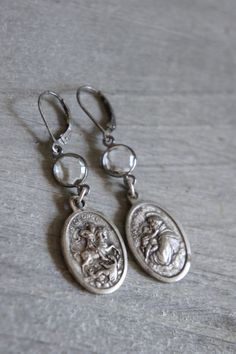 These earrings feature non matching but perfectly paired vintage religious medals, St. George and St. Anthony. The dangle from gorgeous faceted rock crystal connectors set in a bezel of aged sterling silver. Sterling silver ear wires finish off the pair. All handmade and one of a kind.  Length: 1 1/2 from bottom of ear wires.  ***PLEASE read the link below on my shop policies before purchasing*** https://www.etsy.com/shop/frenchfeatherdesigns/policy?ref=shop...