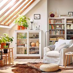 Stor og komfortabel hvit FÄRLÖV lenestol og HEMNES vitrineskap i et hvitt rom med skråtak i glass.