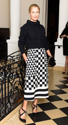 Carolyn Murphy in a black chunky sweater, black and white skirt and black high-heeled pumps.