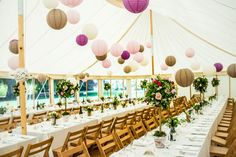 Traditional pole and canvas marquees made in the UK with trestle tables and hanging lanterns. Photography by Pete Henderson