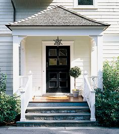 Entry porch with a flared hip roof and simple square columns with curved braces. Dutch door, bluestone steps, cedar porch columns with braces, finial-topped newel posts, and a pair of built-in benches round out the details. This Old House, House With Porch, House Front, Front Entry, Entry Doors, Entrance, Front Doors, Portico Entry, Entry Foyer