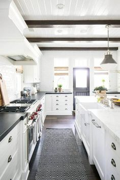 White shaker kitchen cabinets fitted with bronze cup pulls are topped with a black countertop mounted on either side of a Wolf dual range placed against white linear backsplash tiles beneath a white wood French range. ~black counter top and door Dark Wood Kitchens, Modern Farmhouse Kitchens, Cool Kitchens, White Kitchens, Farmhouse Decor, Colonial Kitchen, Industrial Farmhouse, Farmhouse Ideas, Beautiful Kitchen Designs