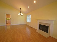 Vaulted living room with fireplace and entry to kitchen