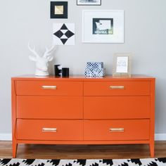 Persimmon paint adds some life to a vintage mid century modern dresser. Brass hardware polished to a shiny gold.