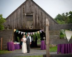 Wedding decor with Purple linens and pennant flags beside the family barn