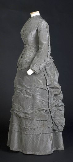 Two-piece day dress, ca. 1875. Silk made from black warp and white weft, making dress shimmering silver. Tight-fitting, boned, long-waisted bodice called cuirass bodice. Nearly all stitching by machine, even binding around the 12 buttonholes. There was probably a white lace collar & cuffs. Little holes at base of neck suggest that owner wore a brooch to close bodice. Smith College Historic Clothing