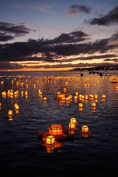 lantern floating, a japanese tradition, is held each memorial day at ala moana beach park, o'ahu; inscribed with messages to loved ones who have passed away, and prayers for a peaceful future, the lanterns--perched atop miniature floating boards--are launched before a shoreline crowd of 40,000+ people