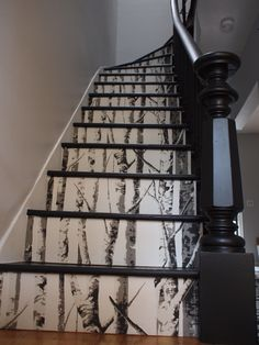An example of the current nature interior design trend - wood wallpapered Staircase.