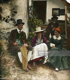 National costumes of Aussee; the woman in the middle with the so called 'Salzhut' (hat) and 'Pfeffertuch' (drapery), the woman on the right is wearing a silken dress and the traditional 'Goldhaube' (gold hood). Salzkammergut. Styria. Hand-colored lantern slide. Around 1905.