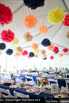 Colorful tissue paper pom poms under a tent. Summer wedding decorations.