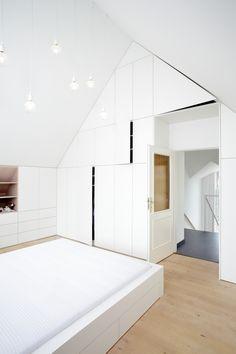 V této podkrovní ložnici bylo třeba vše přizpůsobit tvaru skosených stěn, aby se mohl celý prostor co nejefektivněji využít. Šikmé tvary se tak staly hlavním designovým prvkem celého projektu. Naprostou většinu nábytku tvoří bílé lamino pečlivě lemující okraje zdí a stropu. Úložné prostory jsou pak precizně zasazeny těsně vedle sebe. Tvoří nádherný jednolitý celek, který je narušen jen tehdy, když některá dvířka otevřete. Také postel je tvarována do jednoho bloku. Furniture, Home Decor, Decoration Home, Room Decor, Home Furnishings, Home Interior Design, Home Decoration, Interior Design, Arredamento