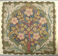 Cushion Cover, 19th century. Design of flowering rose stem surrounded by wreath of oak leaves. Finished on all four sides with fringe in colors used in the embroidery. Designed by William Morris Object ID 18572193