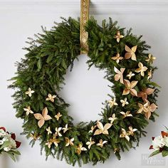 Simple paper flowers are a fun way to dress up a basic evergreen wreath. Make flowers in various shapes and sizes and attach with wire. The flowers on this wreath were made from brown kraft paper and dusted with glitter for a touch of sparkle./
