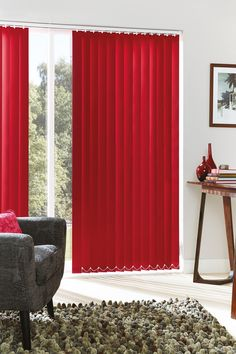 Vertical blinds stack to the sides of the door and will not obstruct the access. Any style of red window treatment will create a warm ambiance in a room.  #redblinds #interiordesign #livingrooms