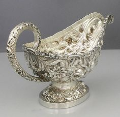 A Stieff sterling silver repousse gravy boat chased with chrysanthemums and roses