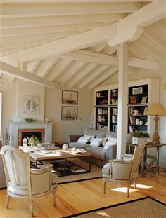 This living room is so lovable with its slanted ceiling, which exposes the cream-painted beams -and  the light, uniform colour adds another layer of airiness to the room.    The decor itself is also fresh and despite some more formal chairs it still remains rather casual -  also the natural sea grass/sisal-type rugs and the light tone of the wood floors help to bring the casual feel to the rather pastel-coloured room.