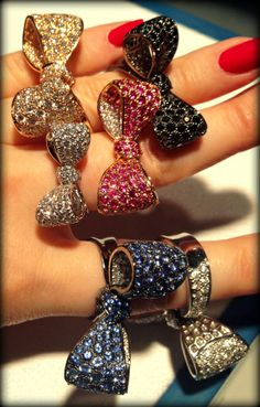 A handful of glorious gold, diamond, and gemstone bow rings by Mimi So. Pictured: diamonds, black diamonds, sapphires, and pink sapphires.
