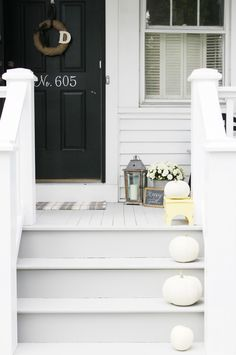 Simple fall decorated porch, white pumpkins, black door