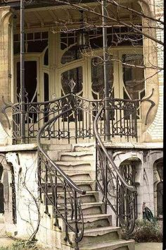 Abandoned home with Art Nouveau windows, doors, and iron railing. I wonder what it looked like inside?