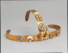 Three-quarter view of a diadem with two gazelle heads, gold, carnelian, turquoise and crizzed glass, excavated from the tomb of Menhet, Menwi, and Merti, three foreign wives of the pharoah Thutmose III (c.1475-1425BC). They were semitic princesses from the Levant, and each one held the title of King's wife. Despite the sumptuous jewelry discovered in their tomb, the absence of the vulture motif on their headdresses indicates they were only minor members of the royal harem.