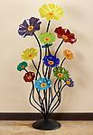 Floor Standing Rainbow Cluster by Scott Johnson and Shawn Johnson. Floor standing cluster of glass flowers on your choice of black or silver stems and base in bright rainbow colors. Coated aluminum stems make this piece perfect for indoor or outdoor display. Each glass glass flower unscrews from the stem. These pieces are suitable for outdoor use. However, the aluminum stems may oxidize in humid climates. Please bring indoors during strong winds, to prevent any damage to the glass. Each…
