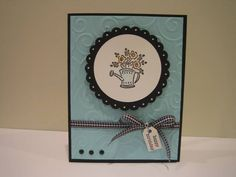 Stamps: Bitty Bouquets Paper: Cool Caribbean, Basic Black, WW Ink: Cool Caribbean, Marigold Morning, True Thyme, Stazon Jet Black Accessories: Aqua Painter, giga scalloped circle punc, CB embossing folder, gingham ribbon, brads, tag Techniques: watercolor