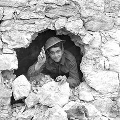 Italy (Misc.) - Private J.A. Robb of The Loyal Edmonton Regiment looking through a shell hole in the foundation of a building, Colle d'Anchise, Italy, 27 October 1943.