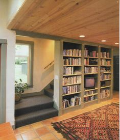 stairway behind bookshelf. Green Tower   Ross Chapin Architects