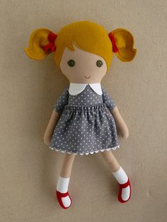 This is a handmade cloth doll measuring 20 inches. She is wearing a sweet, old-fashioned gray and white polka dotted dress with a matching, removable