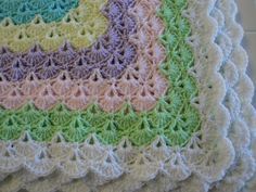 Crocheted baby blanket in multi colors aqua lavender yellow green white pink done in a lacy pattern by AuntieJenniesAttic on Etsy