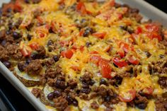 ~Nacho Spuds~  2 large baking potatoes, sliced into 1/2-inch thick rounds;    2 1/2 tbsp. extra virgin olive oil;    Salt & Pepper;    1/2 lb. lean ground beef;    One 15 oz. can black beans, rinsed;    2 tbsp. taco seasoning;    One 8 oz. package shredded sharp cheddar cheese (2 cups);    1 cup chopped tomatoes;    Sour cream; shredded lettuce, for serving