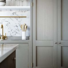 Taupe cabinets, calacatta marble and brass fixtures seem to be trending now. Nice.