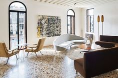 "The large salon in Nikki McCullagh's Venice palazzetto features terrazzo floors and 20th-century tables and seating. ""We wanted to keep the feeling of traditional Venice in the floors, ceilings and architectural details but also speak to Nikki's love of the Italian midcentury modern aesthetic in the furniture,"" said French decorator Jacques Grange."