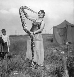 A female snake charmer with the Cole Brothers Circus, watched by two children. #vintage #circus #performers