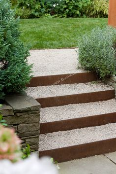 Metal risers and gravel treads make up the unique steps that connect the lower patio area and middle lawn area of this multi-level Seattle backyard.