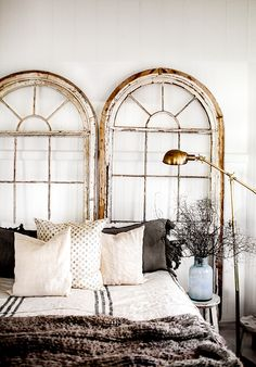 Vintage arch windows used as headboard...love it!