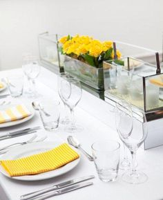 Table linen & centrepieces by Table Art. White weave overlay, yellow printed napkins, rectangle terrarium candle holders. www.tableart.com.au