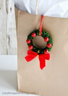 These adorable mini Christmas wreath ornaments are made from shower curtain rings! They make adorable and easy gift wrap adornments, too.