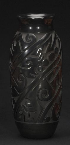 A Santa Clara carved blackware cylinder jar  Tammy Garcia, worked in an allover pattern of complex spiralling design bands below the fluted rim.  height 8 1/2in, diameter 3 3/4in
