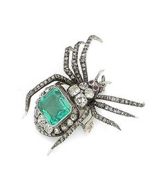An emerald and diamond spider pendant/brooch, circa 1890 Realistically modeled as a spider, the body and legs set with cushion-shaped and rose-cut diamonds, the eyes set with circular cabochon rubies and the body set with a step-cut emerald, suspended from a later fine flattened curb-link chain, cushion-shaped diamonds approx. 2.10cts total, detachable brooch fitting, lengths: pendant 3.8cm, chain 45.5cm (partially illustrated)