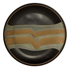 Grande piatto in terracotta con decori a graffio e smalti. Al verso firma dell'autore incussa e marchio della manifattura.