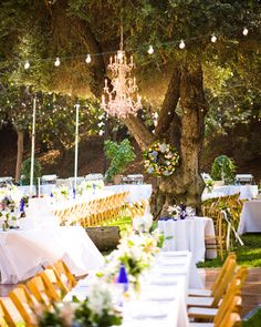 Bistro lights zigzag above the tables, while an elegant chandelier hangs from a central tree
