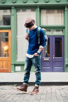 Shop this look on Lookastic: https://lookastic.com/men/looks/crew-neck-sweater-long-sleeve-shirt-jeans-boots-backpack-hat/4066 — Green Backpack — Navy Crew-neck Sweater — White Long Sleeve Shirt — Blue Jeans — Brown Leather Boots — Brown Hat