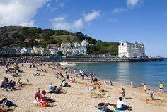 Llandudno in North Wales. The large building on the right is the Grand Hotel with the pier visible and extending out to sea. The greenery above the buildings is part of Happy Valley. Donkey rides along the beach are a common sight together with Punch and Judy shows and lots of happy people. rjp.