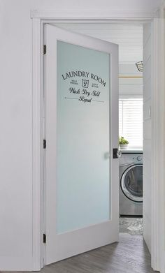 A frosted glass etched door opens to a laundry room fitted with diagonal wood floors, a white shiplap ceiling, and a silver front loading washer and dryer placed beneath a window.