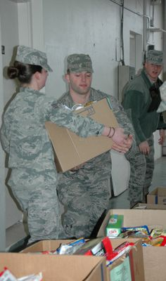 Senior Airman Rachel Bohannon, left, and Senior Airman Christopher Hussey, both with the 446th Civil Engineer Squadron, pick up boxes of food for holiday baskets Dec. 17. Thirty-two boxes of food were donated to the 446th Airlift Wing by the Central Pierce County Fire Department. For the past eight years, these firefighters have supported families in need throughout Pierce County by giving them boxes full of food. (U.S. Air Force Reserve photo by Sandra Pishner)