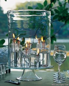 Bottle Beauty - Bars and buffet tables should be adequately lighted, but they're often located far from electrical outlets. An easy, inexpensive solution is to gather clear apothecary bottles and fill them with lamp oil and wicks. Arrange the bottles under a large hurricane for protection; we set these on a sturdy glass cake stand (make sure the bottles are evenly balanced on the stand).
