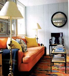 Sag Harbor living room of designer Steven Gambrel - dark wood, circular mirror, orange couch, bright rug, brass accents, pale painted paneling, art in a grid pattern